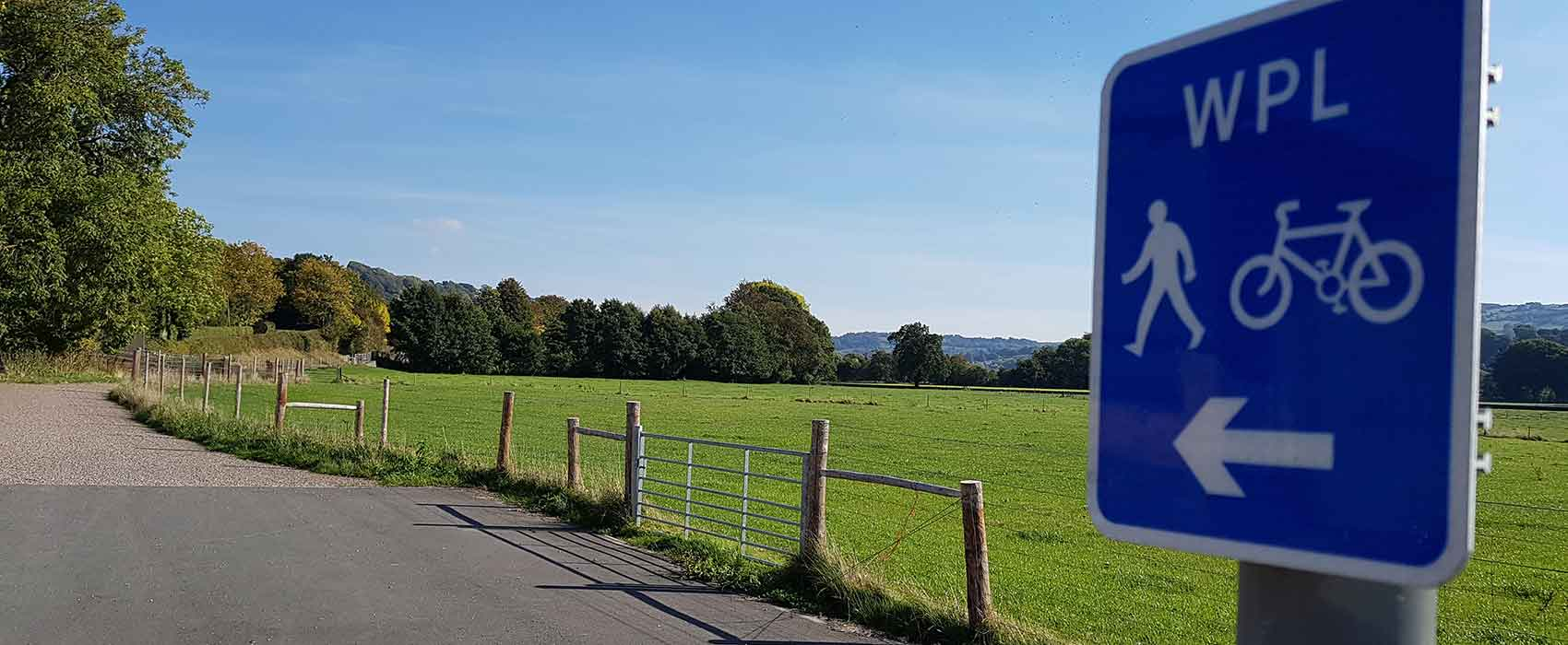 Cycle path and sign among green fields and trees