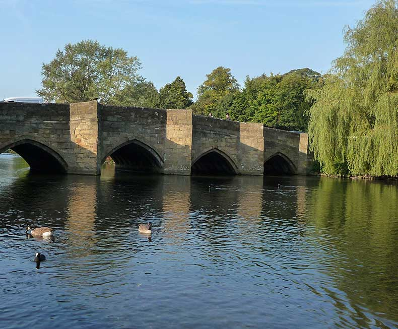 View across the River Wye towards Bakewell bridge, ducks swimming