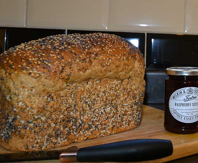 Brown seeded loaf of break with raspberry jam
