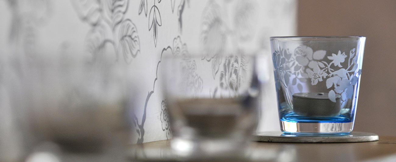 Glass tealight holders against wall-papered wall