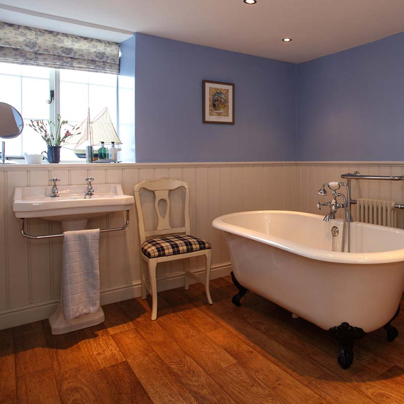 Family blue bathroom with white roll top bath