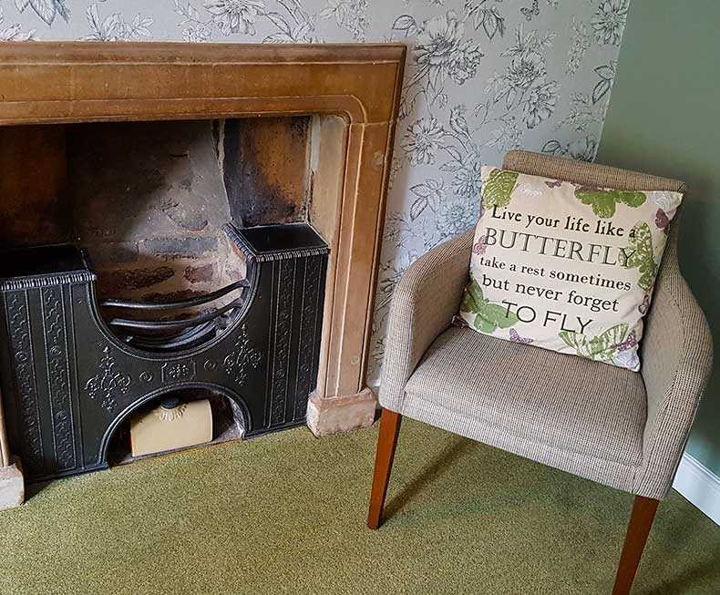 Georgian fireplace with chair beside it