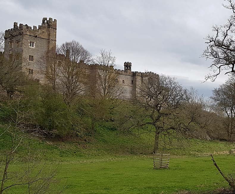 View of Haddon Hall through trees in Winter