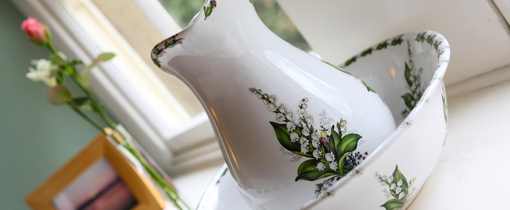 White jug with flowers painted on it with matching bowl