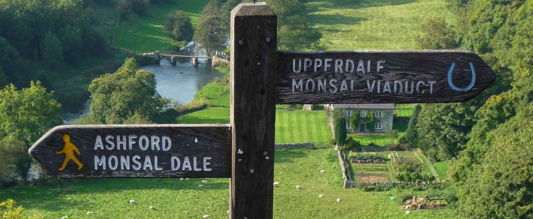 Monsal Dale sign post with fields and river in background