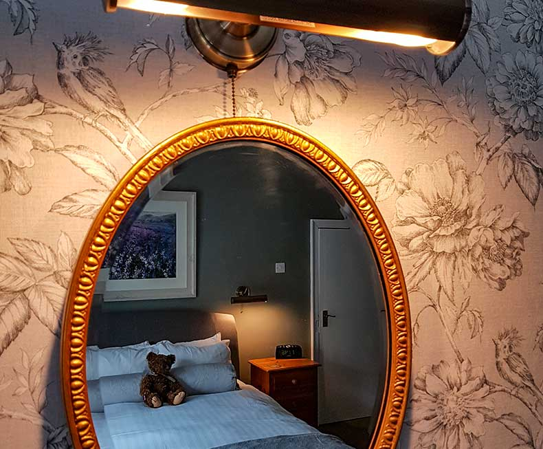 Brass wall light over reflecting oval mirror