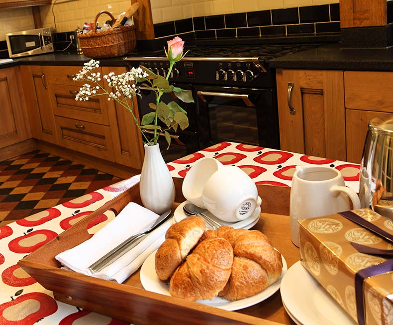 Breakfast tray with croissants, chocolates and flowers