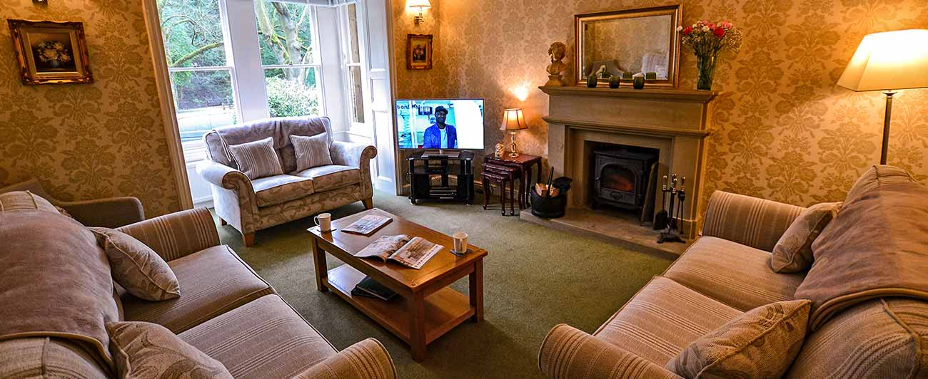 Derwent house sitting room with 3 pale sofas and log fireplace