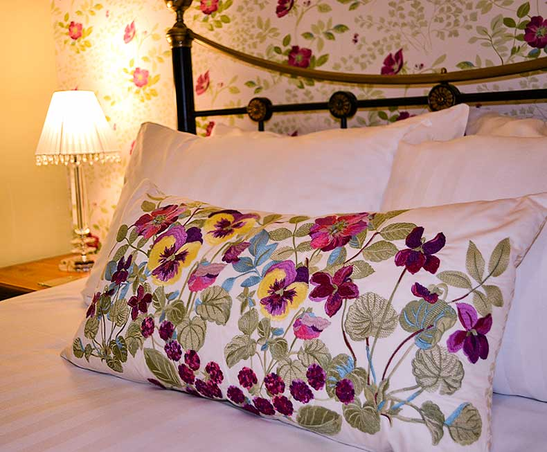 Flowered cushion on antique bed