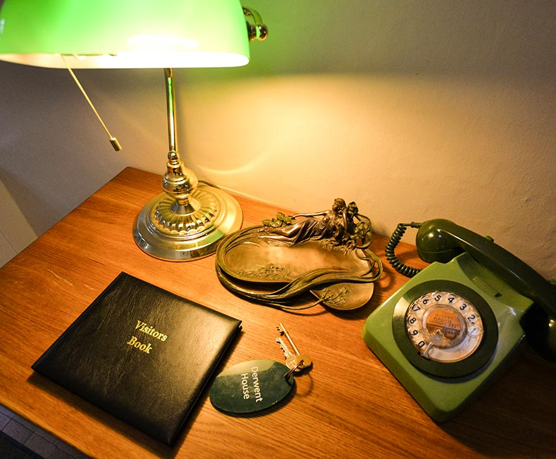 Table with vintage phone, visitors book and vintage green table light