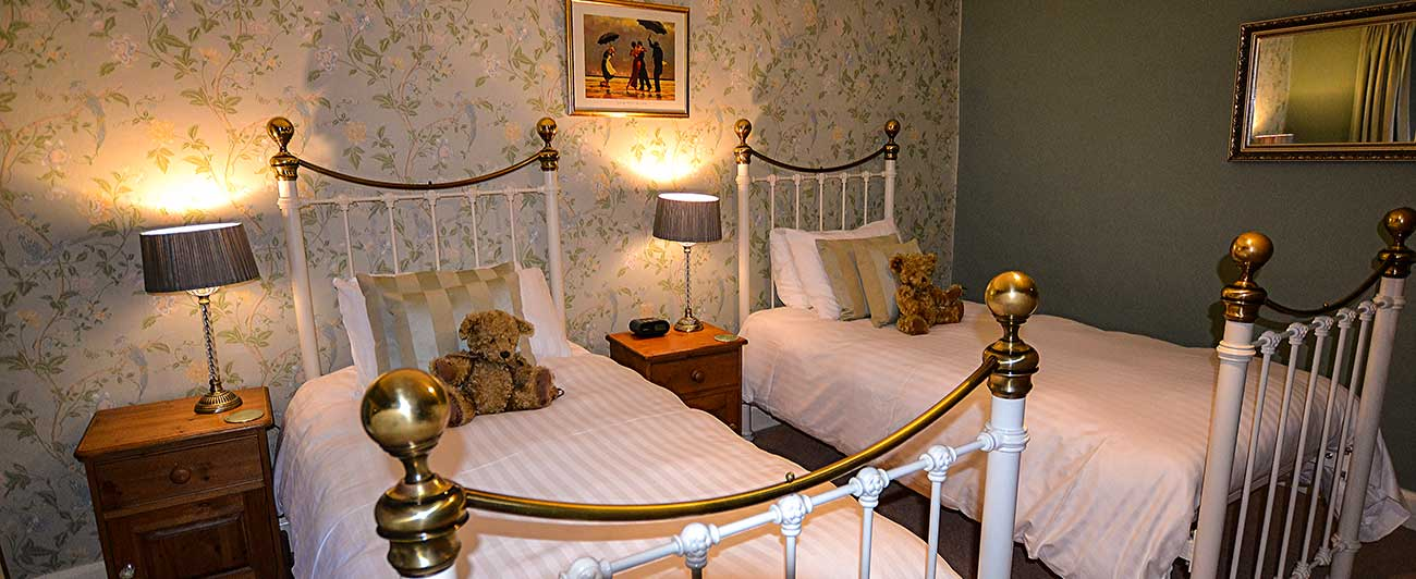 Green twin bedroom with brass beds and teddy bears