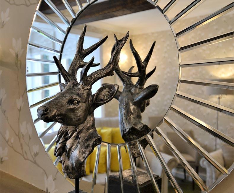 Deer statue and circular mirror