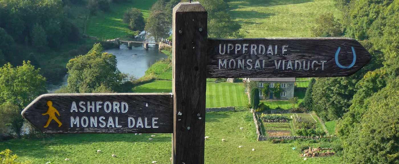 View of Monsal Dale with wooden sign post